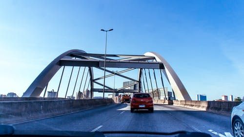 Exterior of contemporary bridge with traffic under clear blue sky through automobile window