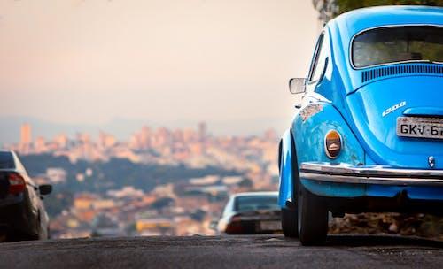 Ground level of parked blue vintage automobile on asphalt highway against cityscape in summer