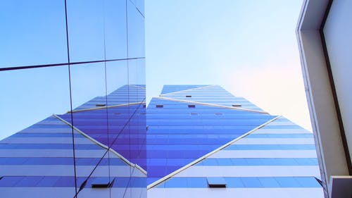 From below of high modern building exterior wall with blue mirrored windows and decorated with triangles on sunny day