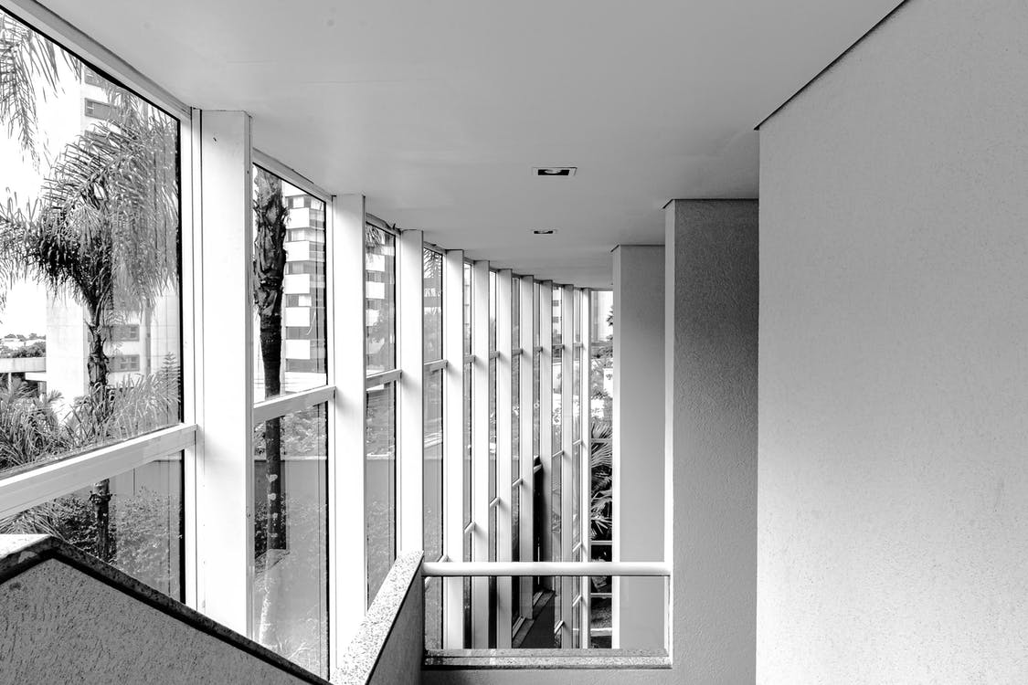 Black and white contemporary building corridor with stairway and big windows in daylight