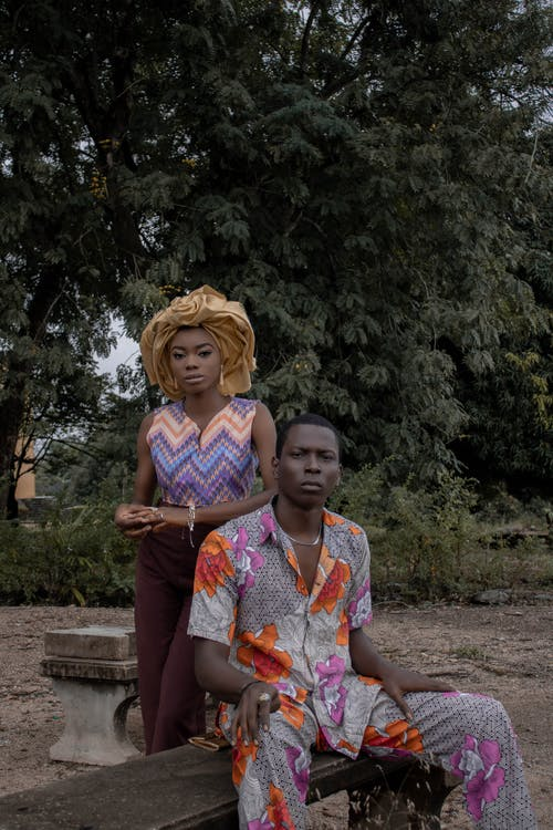 Black couple in nature near tree looking at camera