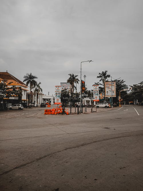 Exterior of tropical town with parked automobiles near asphalt roadway under gloomy cloudy sky