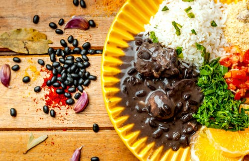 Appetizing black bean stew with rice serves on table