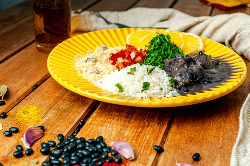 Appetizing traditional Brazilian Feijoada dish of black bean stew served with boiled rice and couscous served on wooden table and decorated with black beans and garlic cloves