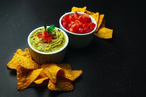 Crispy nachos on black table near guacamole and cut tomatoes