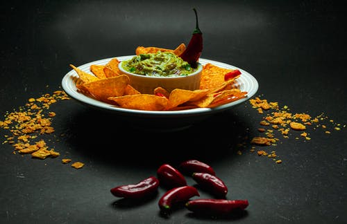 Plate with crunchy nachos and guacamole decorated with chili pepper