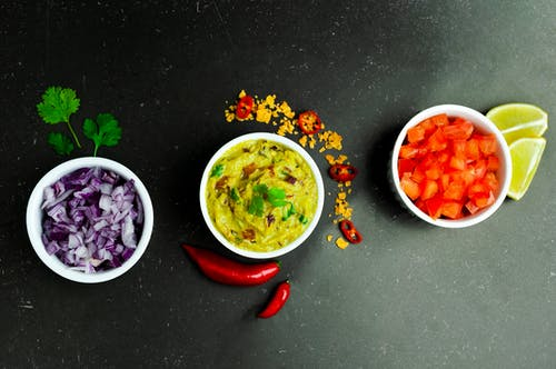 Bowls with guacamole red onion and tomato decorated with spices
