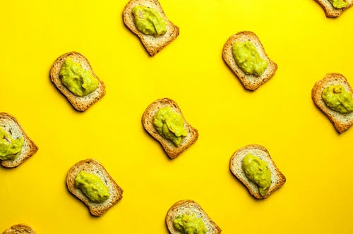 Top view composition of delicious toasts with delectable guacamole placed in rows on yellow background
