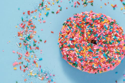 Colorful donut with sprinkles on blue surface