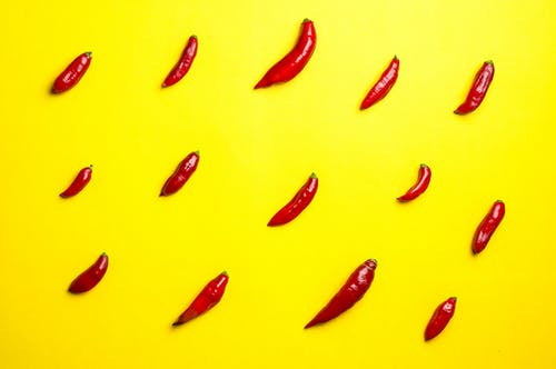 Top view vibrant composition of spicy red chili peppers placed in rows on bright yellow background