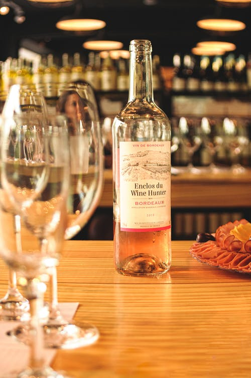 Half empty bottle of sweet rose wine served on restaurant table near wineglasses