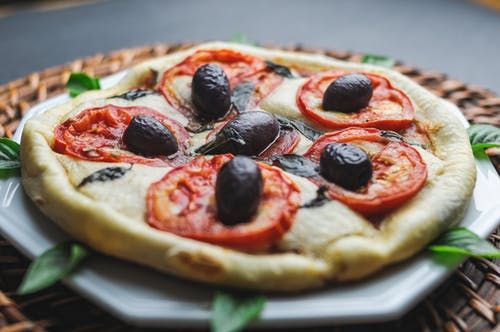 Small pizza with olive and tomato served in plate