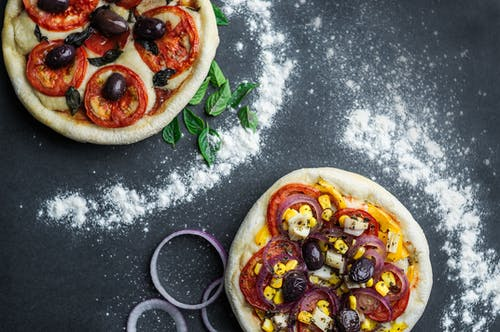 Pizza with tomatoes and cheese on table with flour