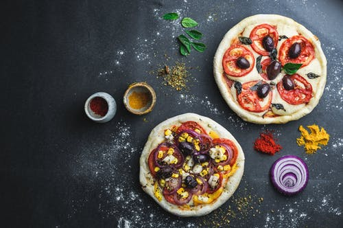 Pizza with vegetables surrounded with flour and condiment