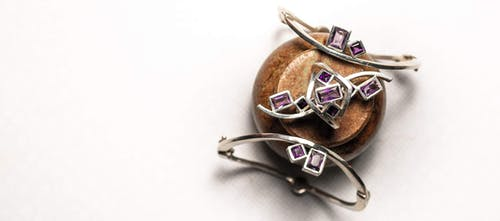 Top view of abstract brooch with gentle violet diamonds attached to beige mineral on white background