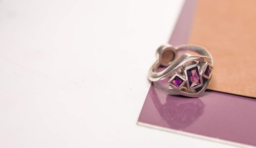 From above of silver ring with bright jewels placed on purple surface with scattered paper