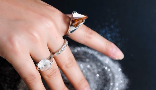 Rings with precious stones on fingers of faceless person