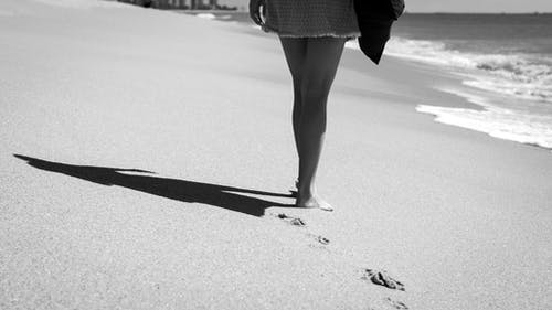 Black and white of faceless barefoot female tourist in dress casting shadow on wet sand and leaving footprints while walking along wavy sea in daytime