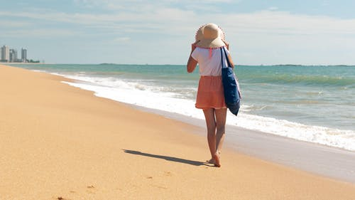 Full body back view of barefoot female traveler in casual clothing adjusting hat while waking on sandy coast of wavy ocean at resort