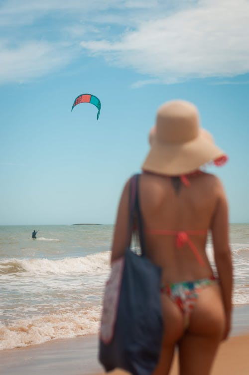Slender woman on sandy beach in daytime