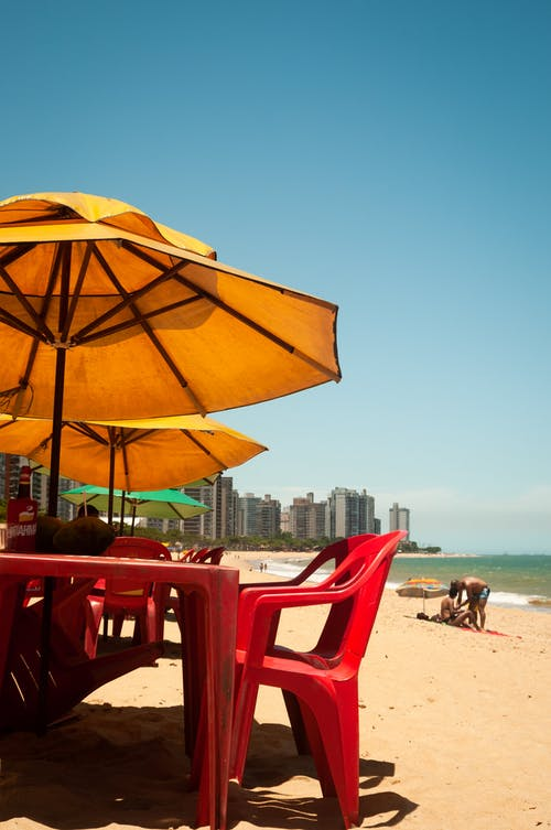 Vivid blue clear sky over rows of yellow parasols over simple red tables and chairs on sandy coast of ocean in sunlight
