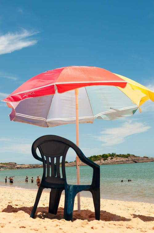 Umbrella over chair on beach
