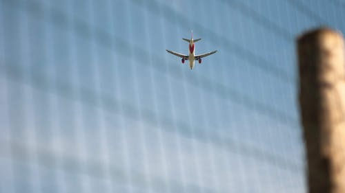 View of aircraft flying in light blue cloudless sky in sunlight through chain link fence