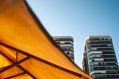 Umbrella and tall building under blue sky