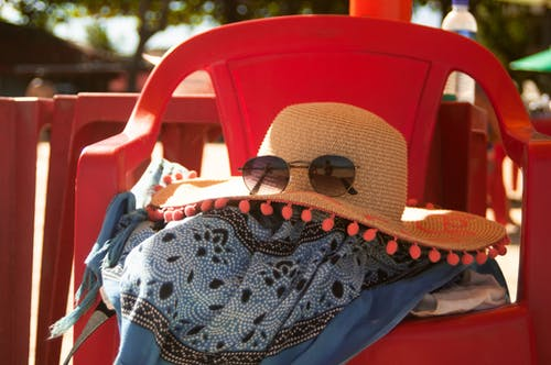 Light beige hat with sunglasses on scarf on simple red chair in sunlight on blurred background