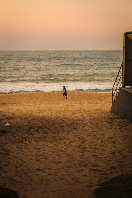 Faceless person on beach near wavy sea