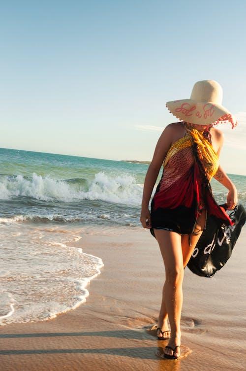 Faceless woman walking on wet seashore