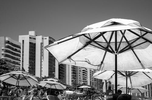 Black and white of umbrellas on terrace of resort hotel with tables and chairs near beach