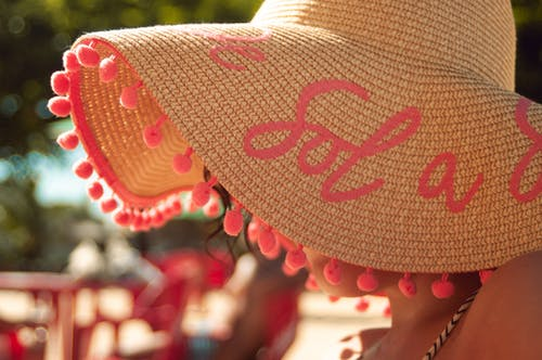 Unrecognizable female in trendy straw hat with brim and pink letters relaxing in tropical resort