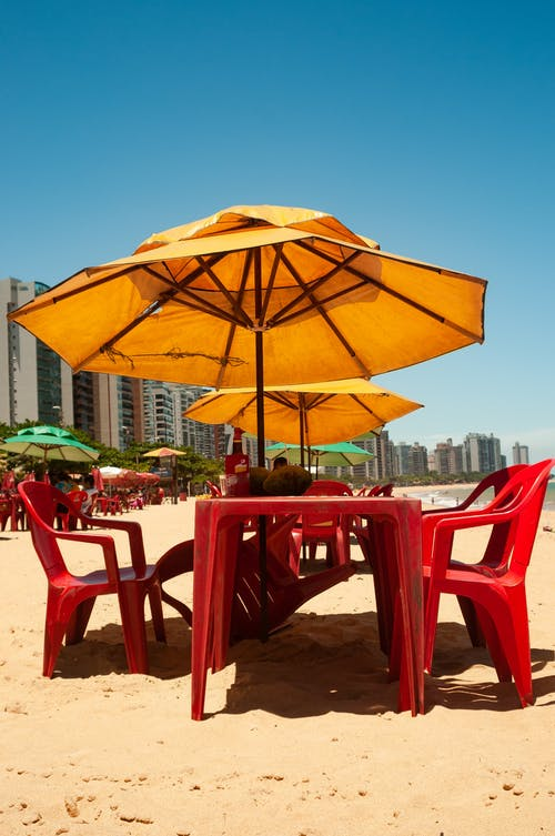 Sandy shore of sea with tables and chairs under yellow umbrellas near resort hotel