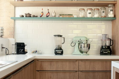 Contemporary kitchen in stylish design with many modern appliances and kitchenware on cabinets