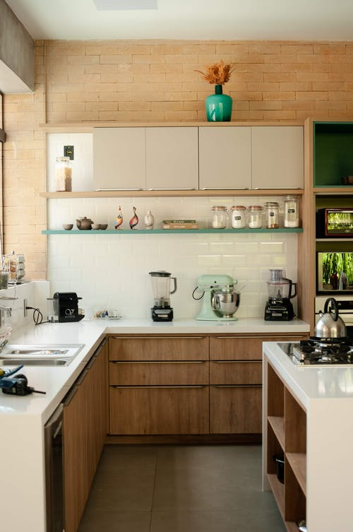 Modern appliance placed on tables of stylish kitchen with wooden furniture in daylight