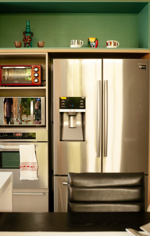 Metallic refrigerator and ovens in modern kitchen