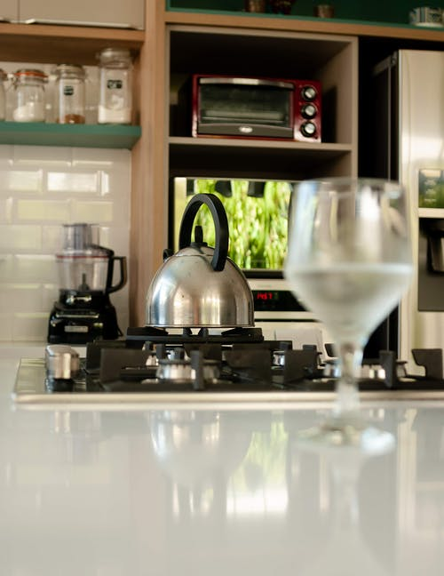 Glass of water placed on white shiny table in modern near stove with metal kettle