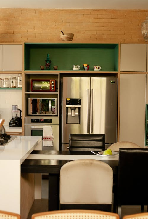Interior of cozy kitchen counter placed in front of stainless steel refrigerator and ovens near cupboard