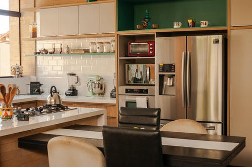 Modern kitchen interior with stainless steel fridge and ovens placed near table and cabinets with contemporary utensils