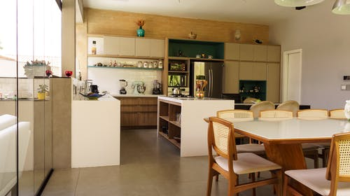 Interior of spacious kitchen with modern wooden furniture and dining zone near panoramic windows in stylish villa