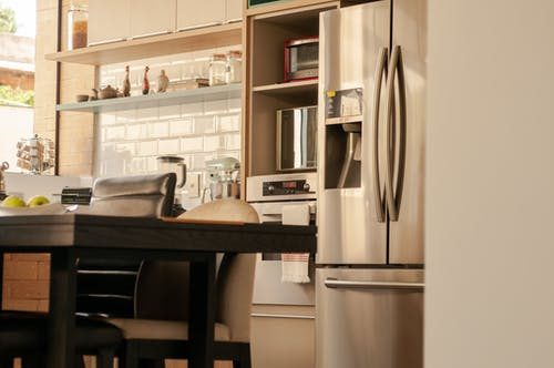 Dining table and chairs placed near fridge and ovens in kitchen