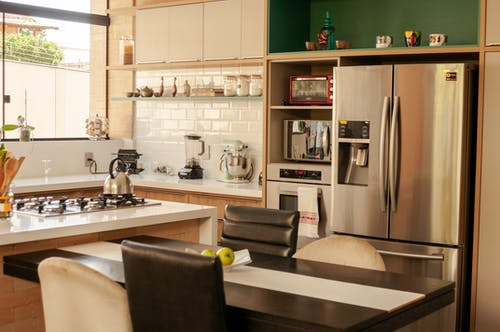 Wooden table with chairs placed in modern kitchen near stylish stainless steel refrigerator and oven in daylight
