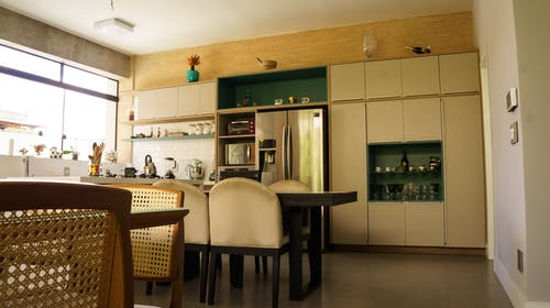 Interior of spacious kitchen with cupboard and dining zones in daylight