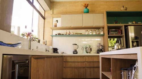 From below wooden cabinets and shelves of cozy kitchen with stainless steel appliances in sunlight