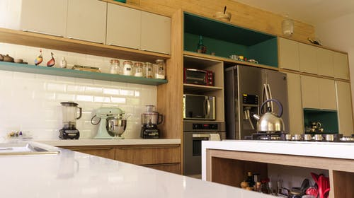 Low angle of modern kitchen interior with spacious cabinets and contemporary appliances in sunlight