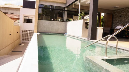 Outdoor swimming pool with clear water in backyard of contemporary villa on sunny day
