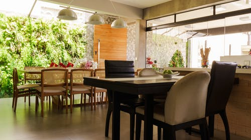 Modern kitchen with stylish dining table and chairs placed near panoramic window overlooking green tropical plants in daylight