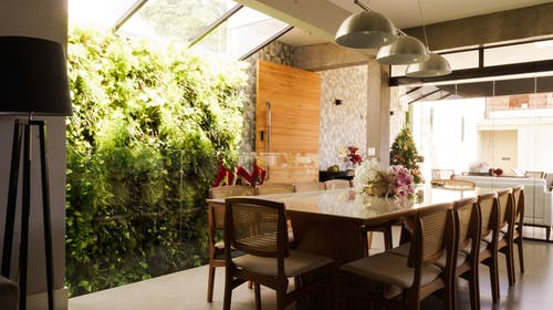 Wooden chairs and dining table decorated with flowers placed near panoramic windows in trendy villa in tropical garden