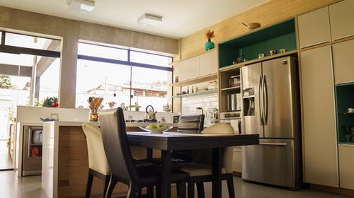 Stylish kitchen interior with dining table and contemporary appliances in daylight